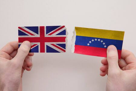 UK and Venezuela paper flags ripped apart. political relationship concept