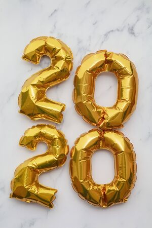 New Year 2020 celebration. Gold foil party balloons on marble background Stock Photo