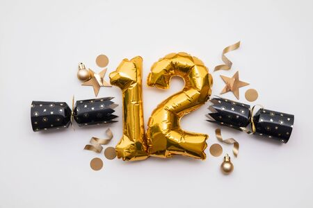 Christmas countdown. Gold number 12 with festive cristmas cracker decorations Stock Photo