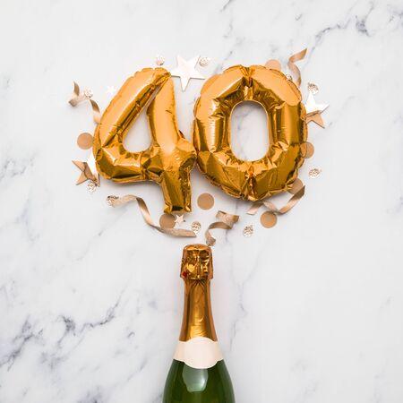 골드 번호 40 풍선이 있는 샴페인 병. 최소한의 파티 기념일 개념 스톡 콘텐츠