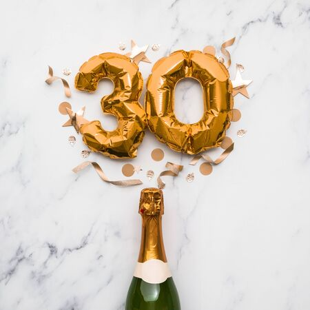 Champagne bottle with gold number 30 balloon. Minimal party anniversary concept
