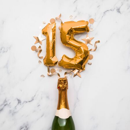 Champagne bottle with gold number 15 balloon. Minimal party anniversary concept
