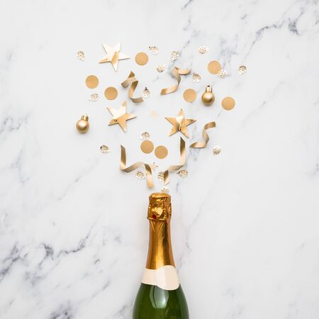 Champagne bottle with gold confetti. Minimal party concept Stock Photo
