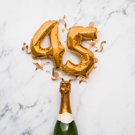 Champagne bottle with gold number 45 balloon. Minimal party anniversary concept