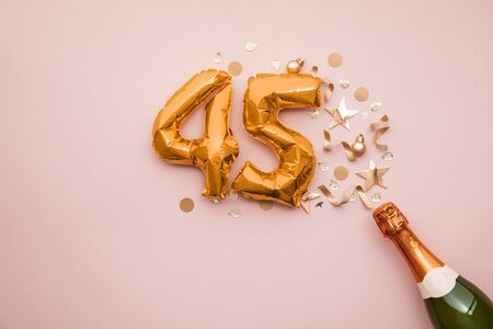 Happy 45th anniversary party. Champagne bottle with gold number balloon.