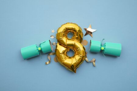 Christmas countdown. Gold number 8 with festive Christmas cracker decorations