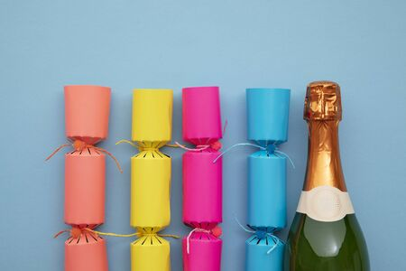 Bright Chritmas crackers with a bottle of champagne