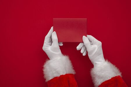 Father Christmas holding a red blank card. Overhead view