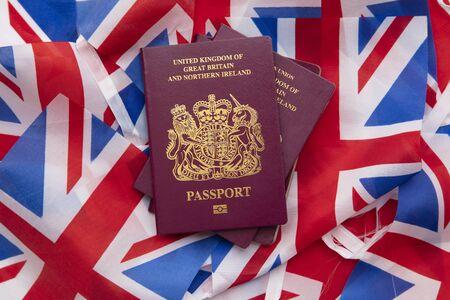 United Kingdom travel passport on a Great Britain Union Jack flag Фото со стока