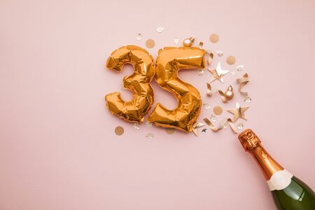 Happy 35th anniversary party. Champagne bottle with gold number balloon.