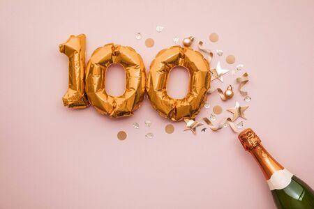 Buona festa per il centenario. Bottiglia di champagne con palloncino con numero d'oro.