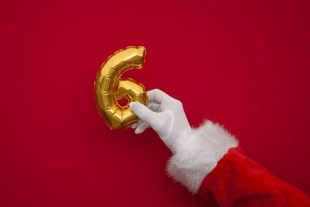 12 days of christmas. Santa hands holding 6th day balloon on red background