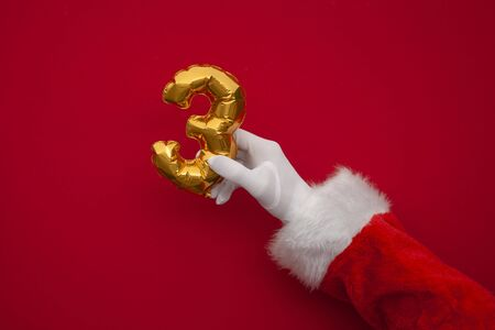 12 days of christmas. Santa hands holding 3rd day balloon on red background