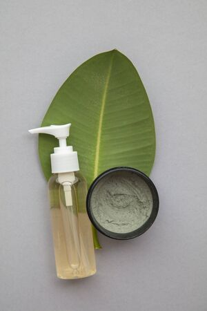 Organic natural cosmetic product with a green leaf on a grey background