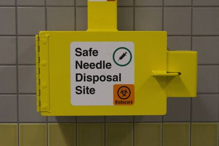 Safe medical needle disposal container on a toilet wall
