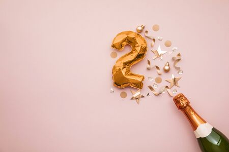 Happy 2nd anniversary party. Champagne bottle with gold number balloon.