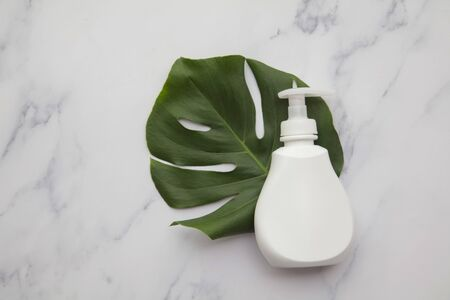 Blank white cosmetic products on a marble background with tropical palm leaf