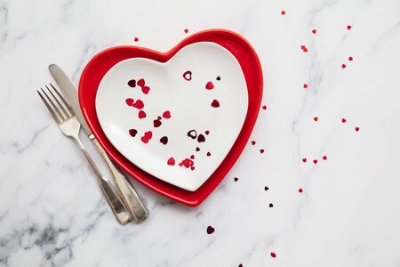 Valentine's day red and white dinner plates with heart shaped confetti