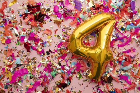 Number 4 gold birthday celebration balloon on a confetti glitter background Stock Photo