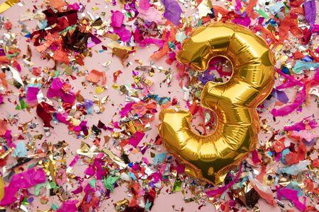 Globo de celebración de cumpleaños número 3 de oro sobre un fondo de brillo de confeti Foto de archivo