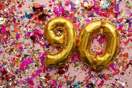 Number 90 gold birthday celebration balloon on a confetti glitter background