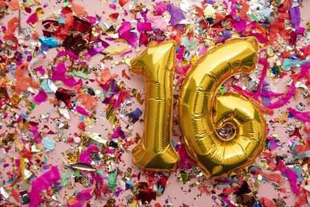 Number 16 gold birthday celebration balloon on a confetti glitter background