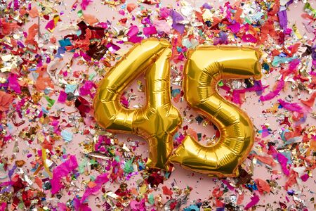 Number 45 gold birthday celebration balloon on a confetti glitter background