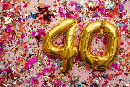 Number 40 gold birthday celebration balloon on a confetti glitter background