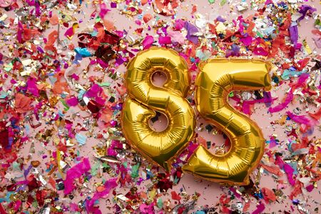 Number 85 gold birthday celebration balloon on a confetti glitter background