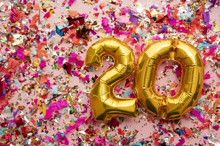 Number 20 gold birthday celebration balloon on a confetti glitter background