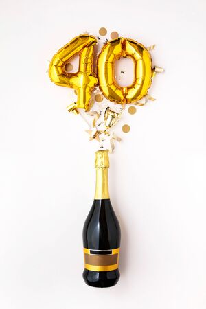 Happy 40th anniversary party. Champagne bottle with gold number balloon.
