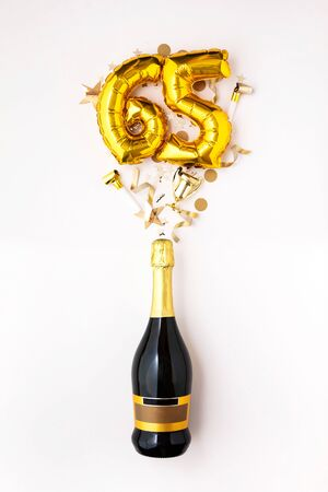 Happy 65th anniversary party. Champagne bottle with gold number balloon. 스톡 콘텐츠