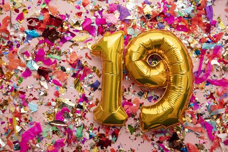 Number 19 gold birthday celebration balloon on a confetti glitter background Stock Photo