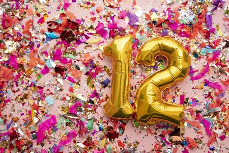 Number 12 gold birthday celebration balloon on a confetti glitter background