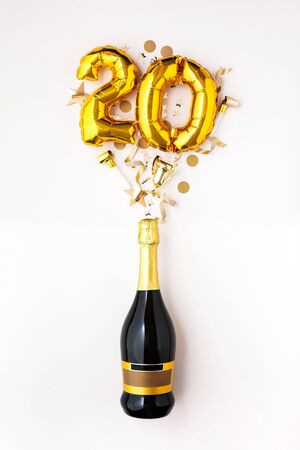 Happy 20th anniversary party. Champagne bottle with gold number balloon.