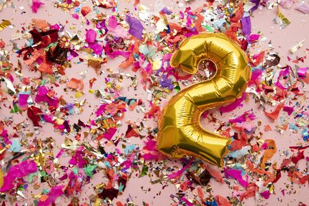 Number 2 gold birthday celebration balloon on a confetti glitter background