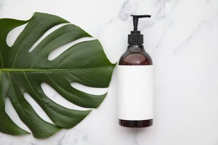Cosmetic product bottle with blank label on a tropical leaf