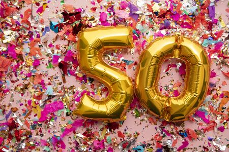 Number 50 gold birthday celebration balloon on a confetti glitter background