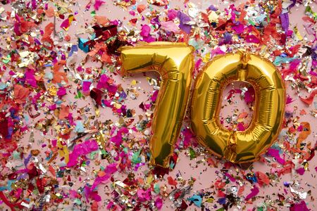 Number 70 gold birthday celebration balloon on a confetti glitter background