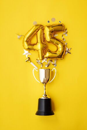 Number 45 gold anniversary celebration balloon exploding from a winning trophy
