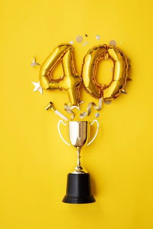 Number 40 gold anniversary celebration balloon exploding from a winning trophy