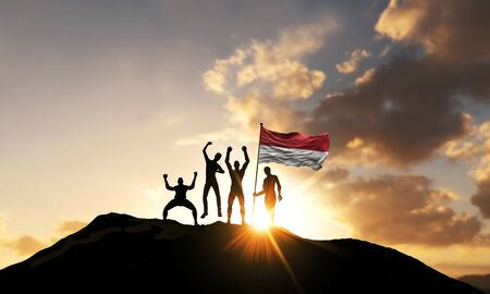 A group of people celebrate on a mountain top with Indonesia flag. 3D Render