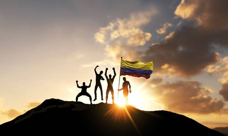 A group of people celebrate on a mountain top with Colombia flag. 3D Render Stock Photo