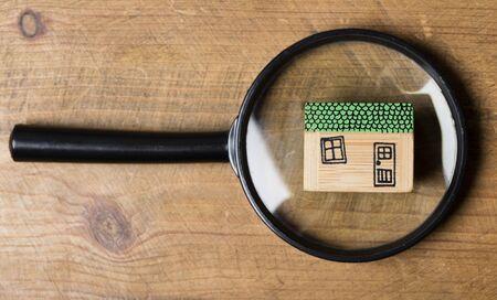 Modèle de maison avec loupe. Concept de recherche de propriété