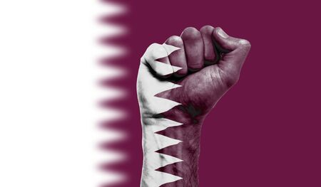 Qatar flag painted on a clenched fist. Strength, Protest concept