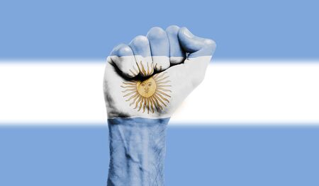 Argentina flag painted on a clenched fist. Strength, Protest concept