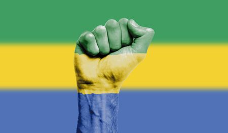 Gabon flag painted on a clenched fist. Strength, Protest concept