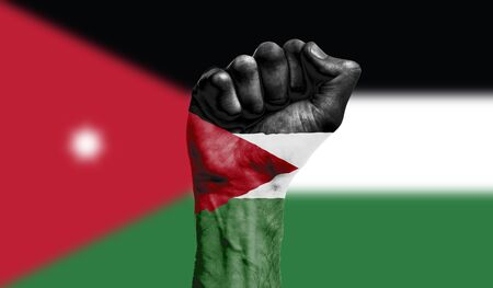 Jordan flag painted on a clenched fist. Strength, Protest concept