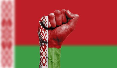 Belarus flag painted on a clenched fist. Strength, Protest concept