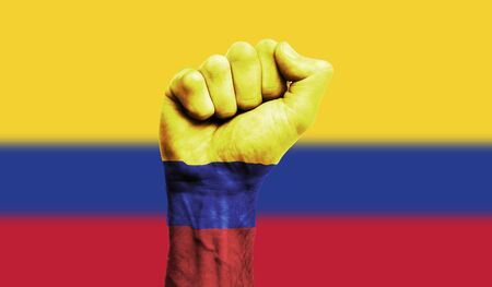 Colombia flag painted on a clenched fist. Strength, Protest concept